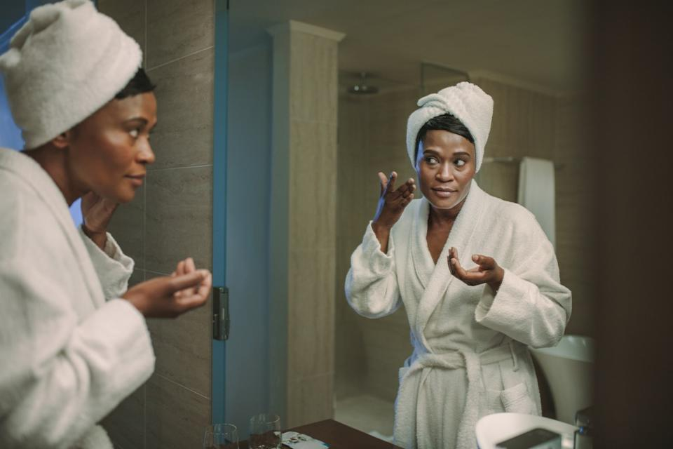 African American Woman Applying Face Cream in the Mirror Silent Health Symptoms