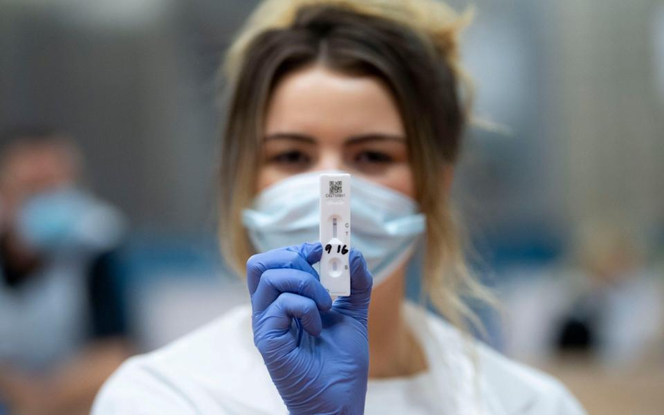 A member of the coronavirus testing staff holds a lateral flow immunoassay device to the camera at Merthyr Tydfil Leisure Centre on November 21, 2020 - Matthew Horwood /Getty Images Europe
