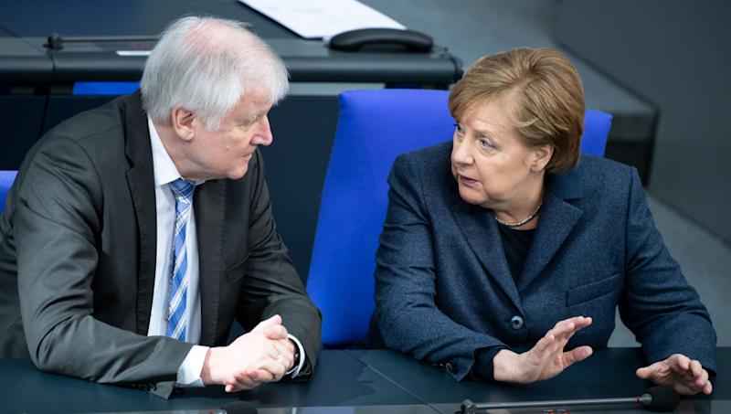 04 March 2020, Berlin: Horst Seehofer (CSU), Federal Minister of the Interior, Home Affairs and Construction, and Chancellor Angela Merkel (CDU) are talking at the beginning of the plenary session in the German Bundestag. The main topics of the 148th session of the 19th legislative period are, in addition to a government statement by the Federal Minister of Health on the coronavirus, the extension of the Bundeswehr mission in Afghanistan and the establishment of a Federal Office for Foreign Affairs. Photo: Bernd von Jutrczenka/dpa (Photo by Bernd von Jutrczenka/picture alliance via Getty Images)