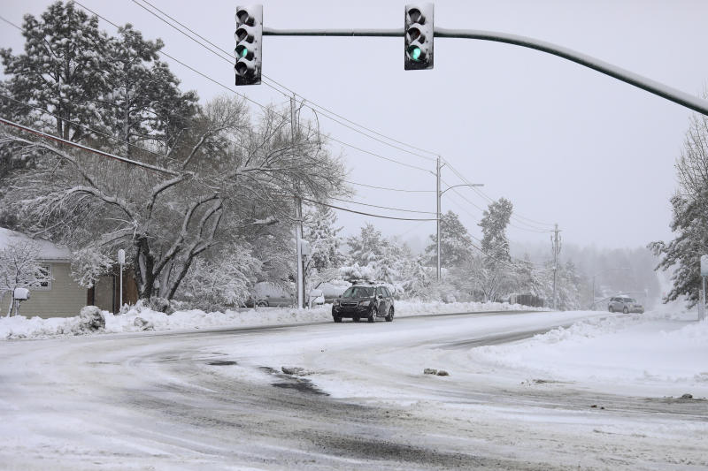 Commuters drive as the snow continues to fall north of downtown Flagstaff, Ariz., Friday, Nov. 29, 2019. A powerful storm making its way east from California is threatening major disruptions during the year's busiest travel weekend, as forecasters warned that intensifying snow and ice could thwart millions across the country hoping to get home after Thanksgiving. The storm has already killed at least one person and shut down highways in the western U.S., stranding drivers in California and prompting authorities in Arizona to plead with travelers to wait out the weather before attempting to travel. (Cody Bashore/Arizona Daily Sun via AP)