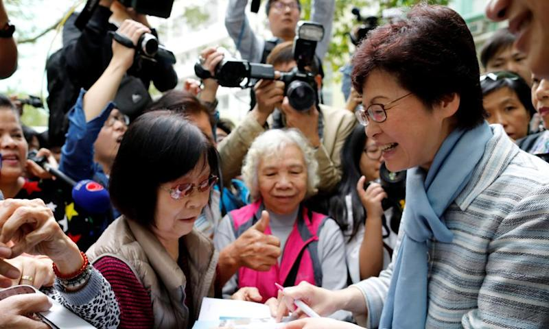 Chief Executive election candidate and former Chief Secretary Carrie Lam signs autographs for supporters during an election campaign