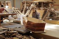 """CORRECTS SPELLING OF NAME A worker constructs coffins at Enzo Wood Designs, in Johannesburg, Wednesday, Sept. 30. 2020. Kasie Pillay, a coffin-maker in South Africa, watched the coronavirus pandemic turn his business upside down. For Pillay, the need for coffins rose and fell as South Africa's lockdown levels changed, but overall, he said, """"business went down."""" As the world surpasses 1 million deaths, Africa is bracing for a likely second wave of infections. (AP Photo/Themba Hadebe)"""