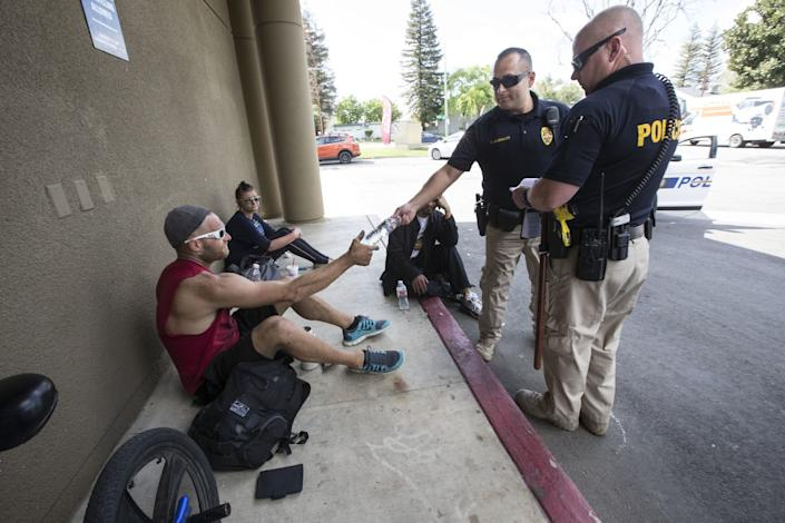 "Bakersfield police officers who are part of a care team that offers water and information to homeless people. <span class=""copyright"">(Alex Horvath / The Californian)</span>"