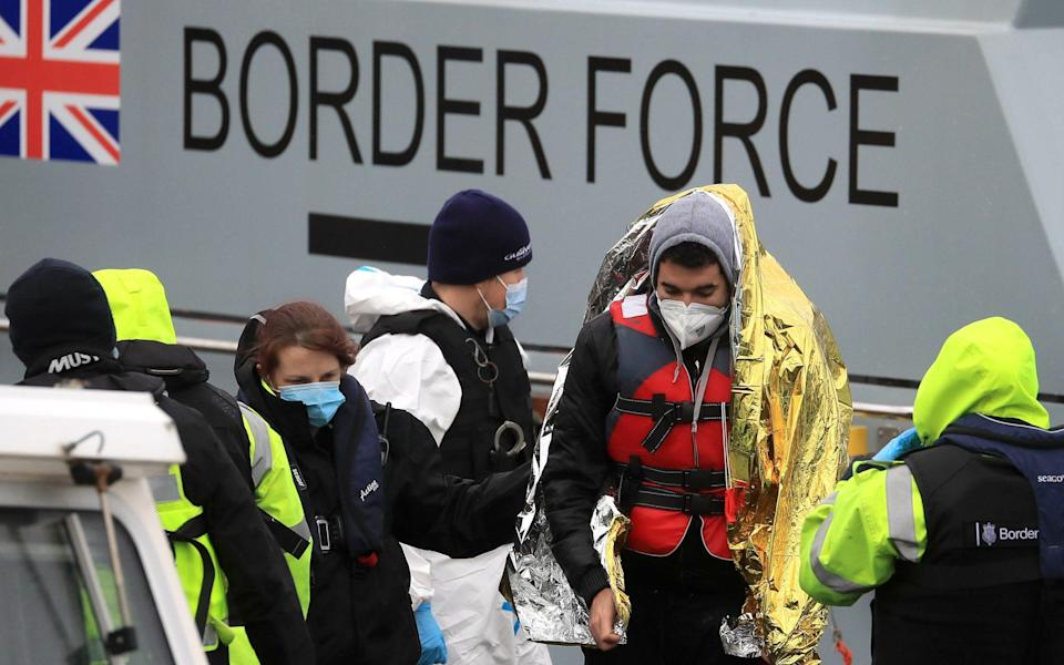 A man is helped by a Border Force officer as a group of people thought to be migrants are brought in to Dover, Kent, onboard a Border Force vessel following a small boat incident in the Channel. - Gareth Fuller/PA