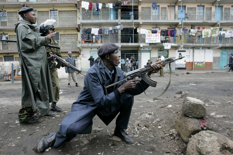 FILE - In this Jan. 20, 2008 file photo, Kenyan police officers react as opposition supporters throw stones at them during post-election violence in the Mathare slum of Nairobi, Kenya. One of Kenya's most vilified institutions - its police force - will be in the spotlight next week after the country's election on Monday, March 4, 2013 as it tries to prevent the same type of post-election bloodbath that Kenya suffered during its last presidential election. (AP Photo/Karel Prinsloo, File)