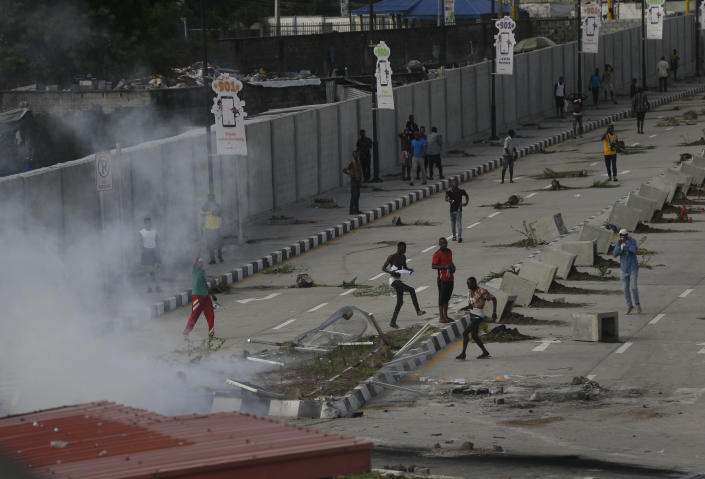 Protesters run away as police officers use teargas to disperse people demonstrating against police brutality in Lagos, Nigeria, Wednesday Oct. 21, 2020. / Credit: Sunday Alamba / AP