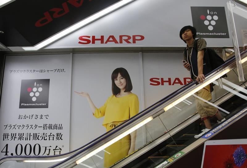 A man rides an escalator past Sharp Corp's advertisements at an electronics retail store in Tokyo