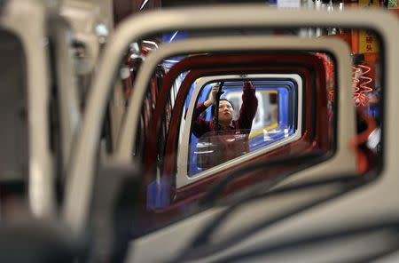 A worker installs rubber onto the windows of the doors along a production line at a truck factory of Anhui Jianghuai Automobile Co. Ltd in Hefei