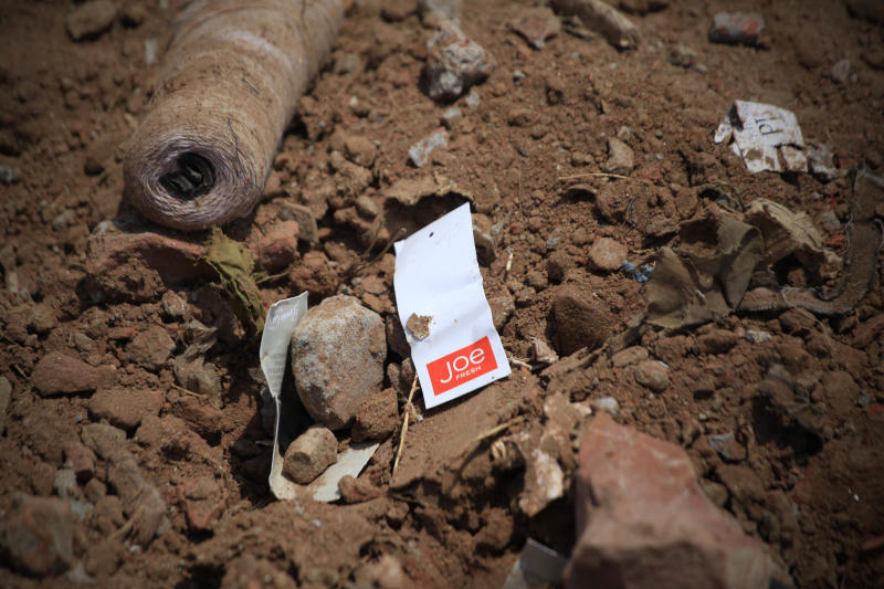A clothes tag lies in the rubble of a garments factory that collapsed in Savar near Dhaka, Bangladesh, Friday, May 3, 2013. More than 500 bodies have been recovered from the debris of the building, even as the Bangladeshi government suspended Savar's mayor and arrested an engineer who had called for the building's evacuation last week, but was also accused of helping the owner add three illegal floors to the eight-story structure. (AP Photo/Ismail Ferdous)