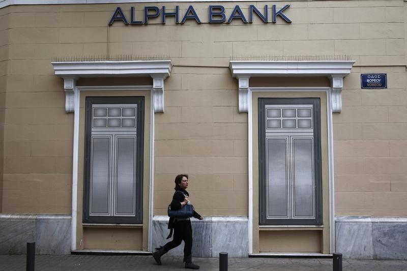 A woman makes her way past the logo of Alpha Bank in Athens