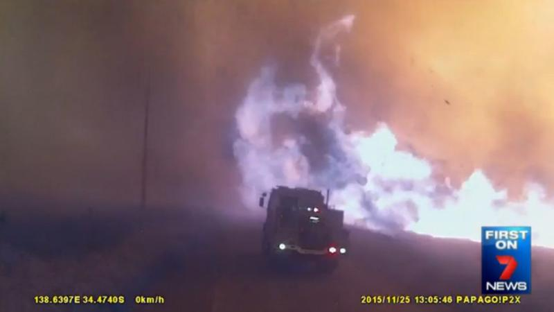 The first truck reverses in a panic as flames reach the edge of the road. Photo: 7News