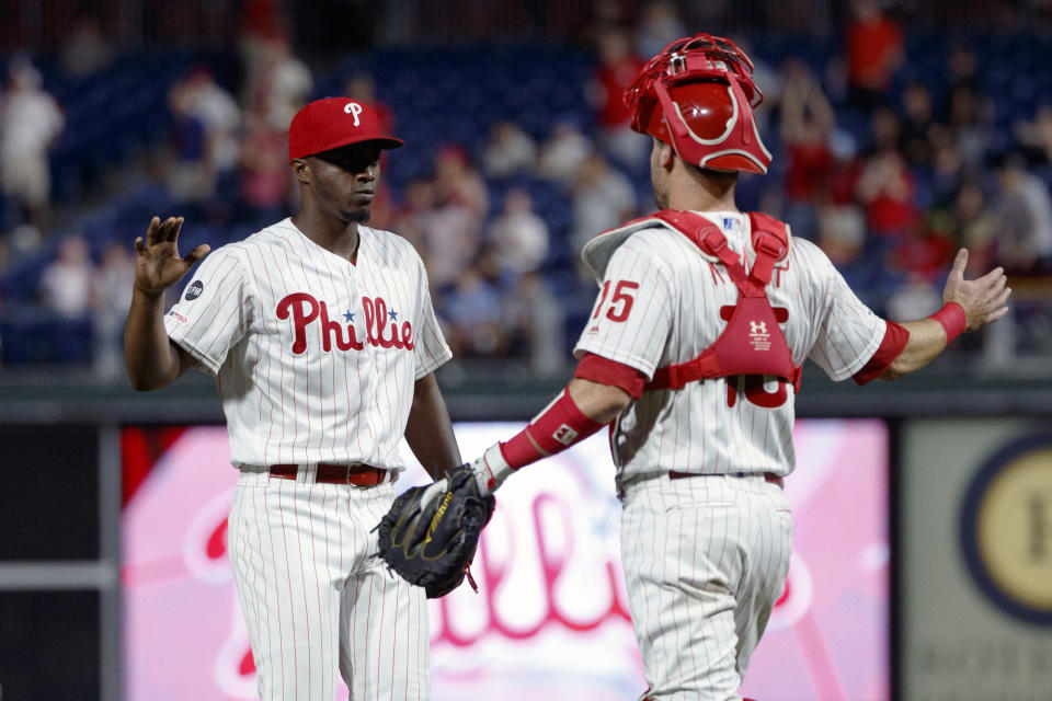 Philadelphia Phillies relief pitcher Edgar Garcia, left, and catcher Andrew Knapp celebrate after a baseball game against the Pittsburgh Pirates, Wednesday, Aug. 28, 2019, in Philadelphia. Philadelphia won 12-3. (AP Photo/Matt Slocum)