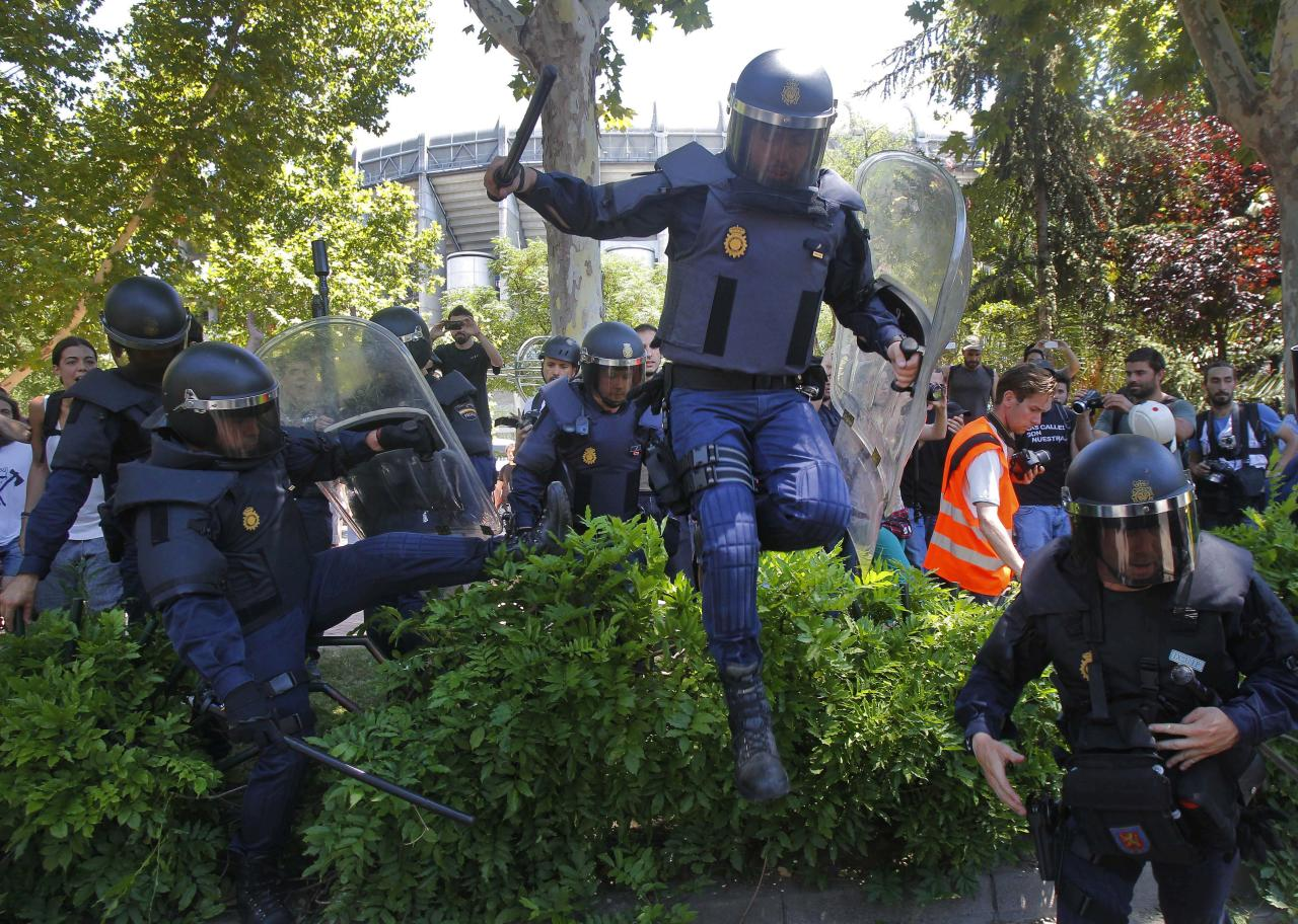 Police riots run after the demonstrators during the coal miners's march to the Minister of Industry building in Madrid, Wednesday, July 11, 2012. Coal miners angered by huge cuts in subsidies converged on Madrid  for protest rallies after walking nearly three weeks under a blazing sun from the pits where they eke out a living. (AP Photo/Andres Kudacki)