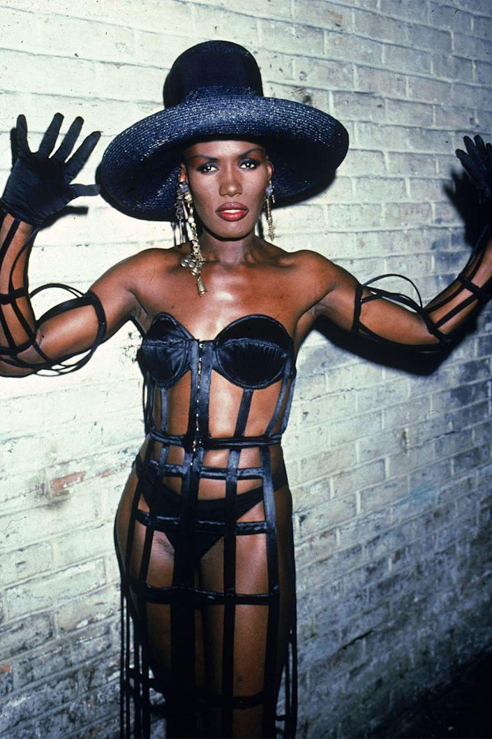 <p>Grace Jones in a caged black look and hat for a performance. </p>