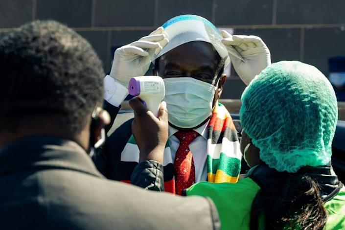 Zimbabwe's President Emmerson Mnangagwa wears a protective facemask and has his temperature taken, as the southern African country has seen coronavirus cases surge in recent weeks