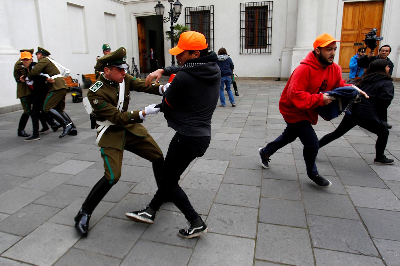Police guards attempt to detain demonstrators during a protest inside the government house against the government's education reform in Santiago, Chile, May 24, 2016. REUTERS/Stringer FOR EDITORIAL USE ONLY. NO RESALES. NO ARCHIVE. CHILE OUT. NO COMMERCIAL OR EDITORIAL SALES IN CHILE     TPX IMAGES OF THE DAY