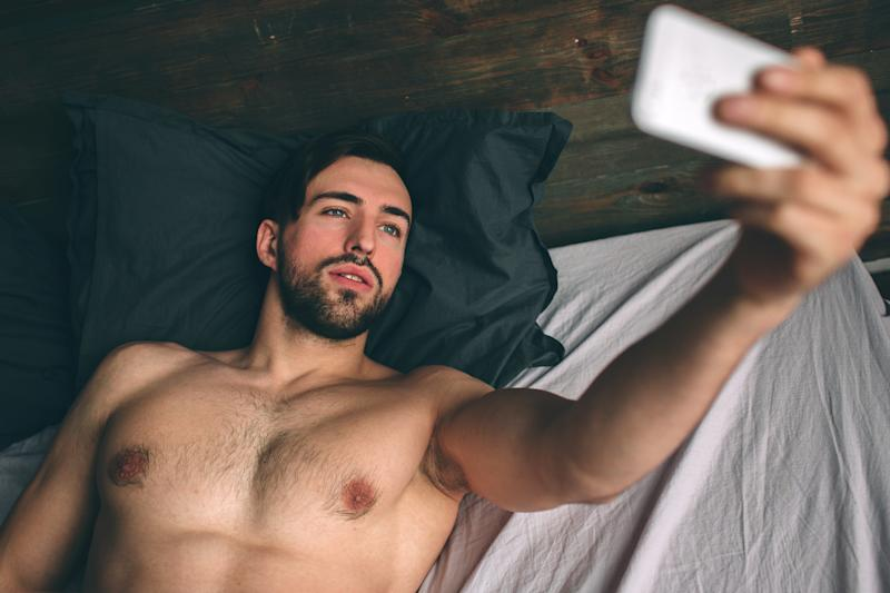 Naked bearded dark-hair handsome man shirtless in white bed taking a selfie.