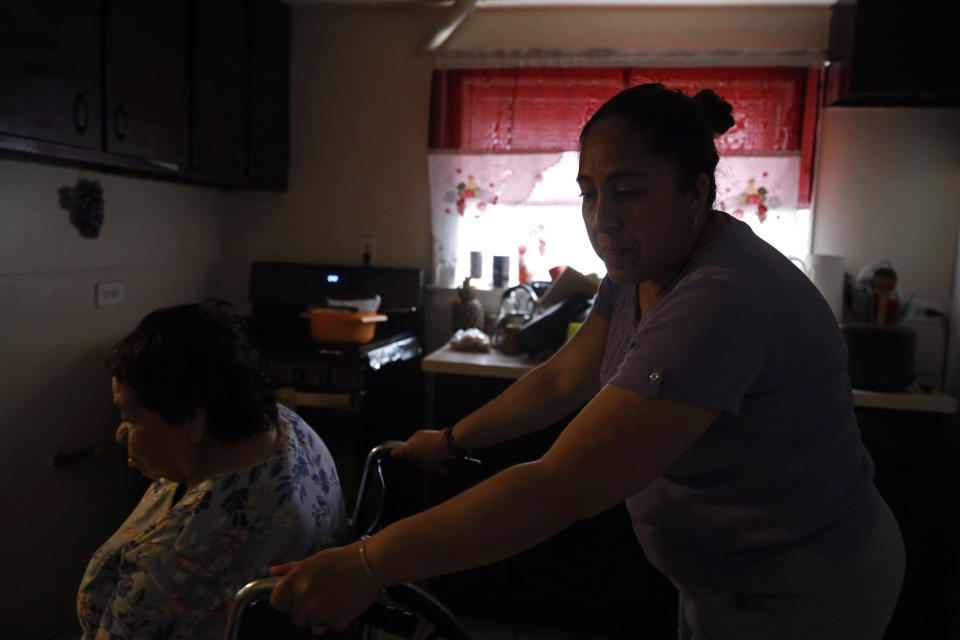 Eugenia Rodriguez, right, maneuvers the wheelchair with her 84-year-old mother, Francisca Perez, who suffers from a heart condition, rheumatoid arthritis and depression, among other ailments, Wednesday, June 30, 2021, in their house in Chicago's Little Village neighborhood. Rodriguez hasn't been eligible for insurance coverage after overstaying a visitor visa from Mexico. She used to wake up every two or three hours at night to check on her mother. Since getting health insurance through the Illinois program, her mother has all the medications she needs. (AP Photo/Shafkat Anowar)