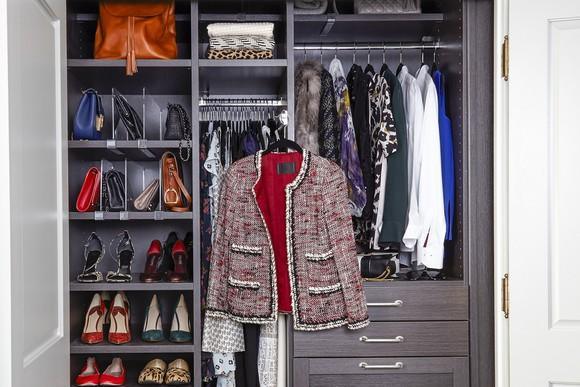 Closet with multiple shelves and plenty of shoes, blouses, and other clothing.