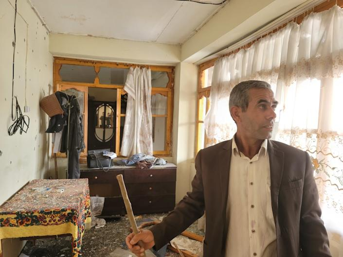 Firidun Kadimov clears debris from inside his home after it was struck by a missile in Tezekend, Azerbaijan