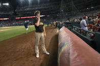 San Diego Padres' Wil Myers talks on a cell phone during a stoppage in play due to an incident near the ballpark during the sixth inning of a baseball game between the Washington Nationals and the Padres, Saturday, July 17, 2021, in Washington. (AP Photo/Nick Wass)