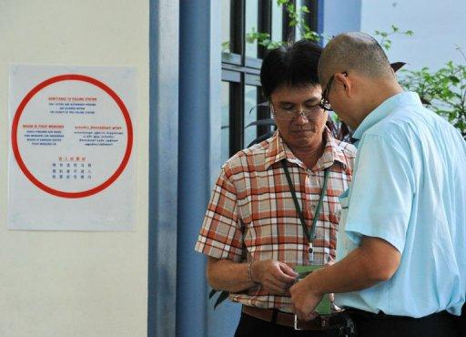 A presiding officer (L) checks a voter polling card at a polling centre in Singapore. Singapore's ruling People's Action Party (PAP) was returned to power on Sunday with a huge majority but lost a key district to the opposition, costing a senior cabinet minister his job