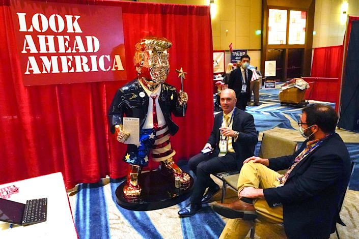 Look Ahead America sponsor Matt Braynard, center, talks to conference attendees at his booth in the merchandise show with a statue of former president Donald Trump at the Conservative Political Action Conference (CPAC) in Orlando, Florida.
