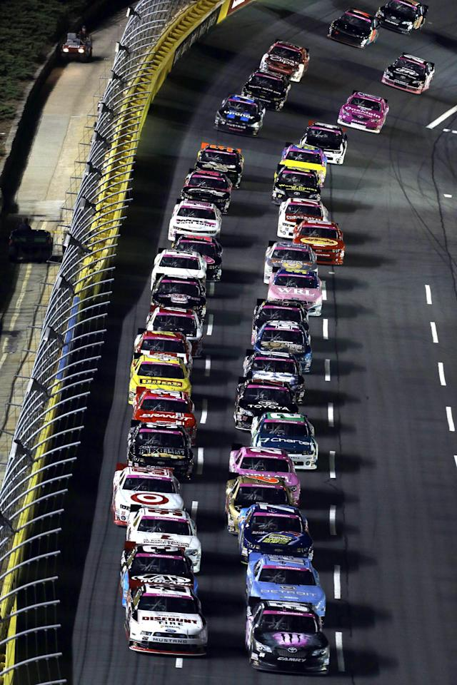 Drivers make their way down the front stretch to begin the NASCAR Nationwide Series auto race at Charlotte Motor Speedway in Concord, N.C., Friday, Oct. 11, 2013. (AP Photo/Gerry Broome)