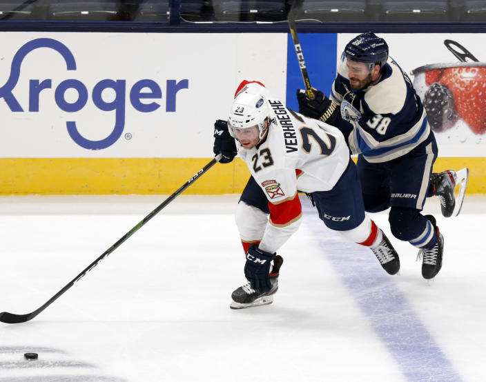 Florida Panthers forward Carter Verhaeghe, left, controls the puck next to Columbus Blue Jackets forward Boone Jenner during the first period of an NHL hockey game in Columbus, Ohio, Tuesday, Jan. 26, 2021. (AP Photo/Paul Vernon)