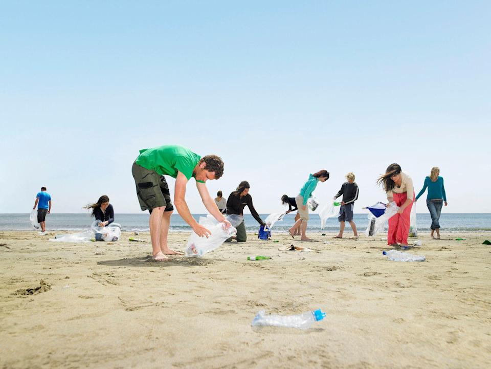 Young people collecting rubbish on a beach in Cornwall (Getty Images)