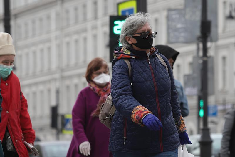 A woman wearing a face mask as a precaution, crosses the street during the covid 19 pandemic. Russian President, Vladimir Putin extends off-work days till 11 May as at least 93 558 confirmed cases and 867 death by the corona virus disease have been recorded in Russia. (Photo by Sergei Mikhailichenko / SOPA Images/Sipa USA)