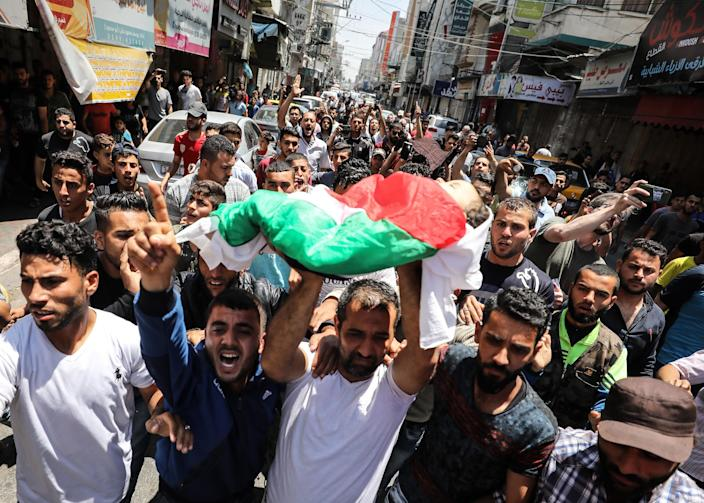 <p>Palestinian mourners carry the body of eight-month-old Palestinian baby Leila Anwar Ghandoour, died from tear gas inhalation during clashes in Gaza the previous day, during her funeral in Gaza City on May 15, 2018. (Photo: Mustafa Hassona/Anadolu Agency/Getty Images) </p>