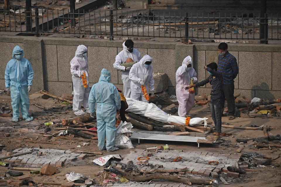 Relatives and friends, wearing PPE suits, prepare a body for cremation in New Delhi today (AFP via Getty Images)