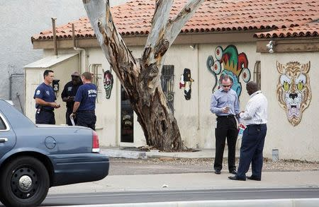Police confer near a tattoo parlor at one of the scenes of a multiple location shooting that has injured at least four people in Mesa, Arizona March 18, 2015.  REUTERS/Deanna Dent