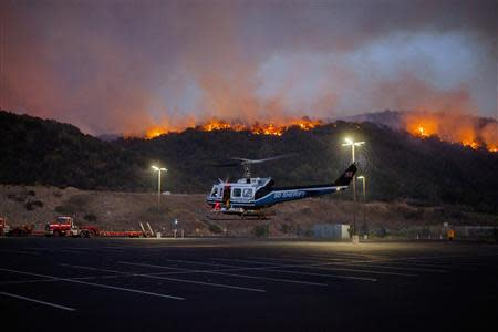 A helicopter is seen as firefighters battle a blaze in San Marcos, California May 14, 2014. REUTERS/Sam Hodgson