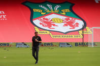 """In this photo provided by Wrexham FC, Wrexham manager Phil Parkinson is seen in front of the new Kop banner the Racecourse Ground in Wrexham, Wales, Saturday, Sept. 18, 2021. It has been described as a """"crash course in football club ownership"""" and the two Hollywood stars who bought a beleaguered team in English soccer's fifth tier with the lofty aim of transforming it into a global force are certainly learning on the job.(Gemma Thomas/Wrexham FC via AP)"""