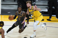 Los Angeles Lakers guard Dennis Schroeder, left, drives against Indiana Pacers forward Domantas Sabonis during the first half of an NBA basketball game Friday, March 12, 2021, in Los Angeles. (AP Photo/Marcio Jose Sanchez)