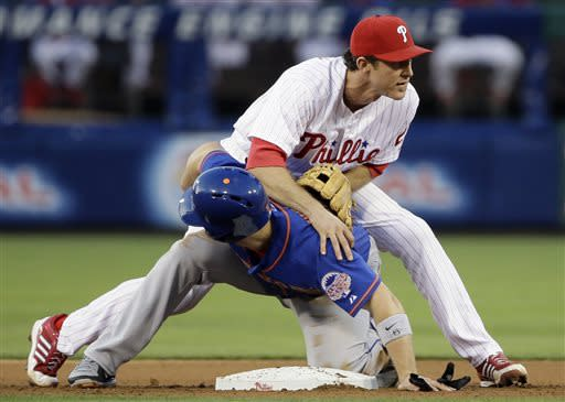 Philadelphia Phillies second baseman Chase Utley, top, and New York Mets' David Wright collide after Wright was forced out at second on a fielder's choice by Marlon Byrd in the fourth inning of a baseball game on Friday, June 21, 2013, in Philadelphia. Byrd was safe at first on the play. (AP Photo/Matt Slocum)