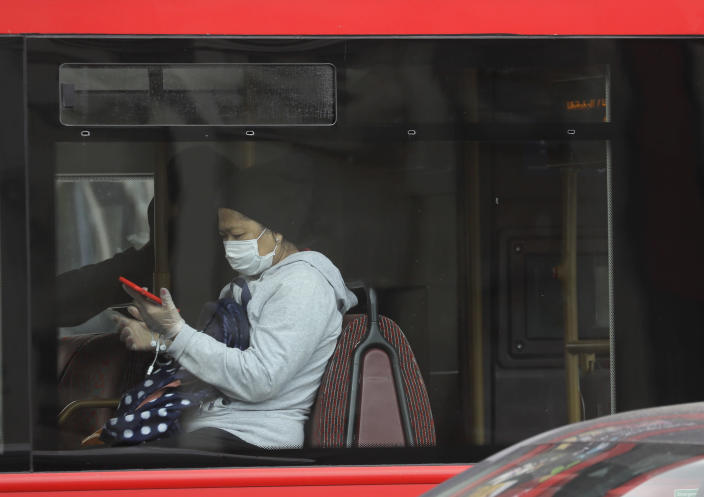 A bus passenger wears a mask as she travels in London, Friday, June 5, 2020. It will become compulsory to wear face coverings whilst using public transport in England from Monday June 15. (AP Photo/Kirsty Wigglesworth)