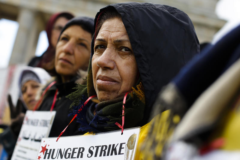 Supporters of the National Council of Resistance of Iran attend a hunger strike in protest against the situation in the Ashraf and Liberty Camps near Baghdad, in front of the Brandenburg Gate in Berlin, Germany, Friday, Oct. 18, 2013. (AP Photo/Markus Schreiber)