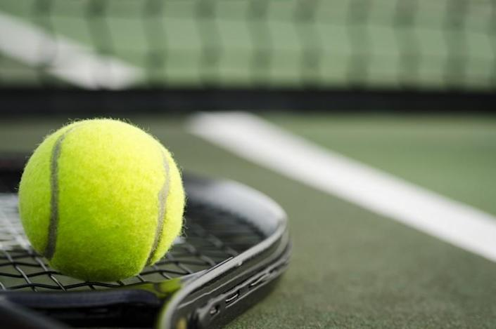 A black tennis racket and yellow tennis ball laying on the ground at a tennis court in early morning light.