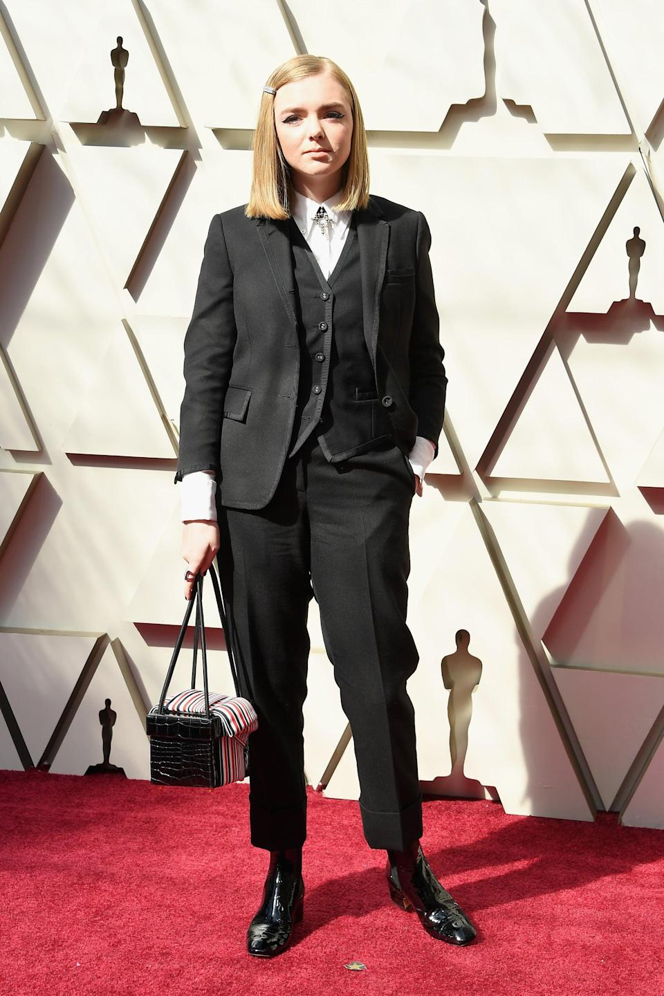 <p>Wearing a three-piece suit.</p>