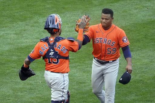 Houston Astros pitcher Framber Valdez, right, and catcher Martin Maldenado celebrate as the Astros beat the Minnesota Twins 4-1 in Game 1 of an American League wild-card baseball series, Tuesday Sept. 29, 2020, in Minneapolis. (AP Photo/Jim Mone)