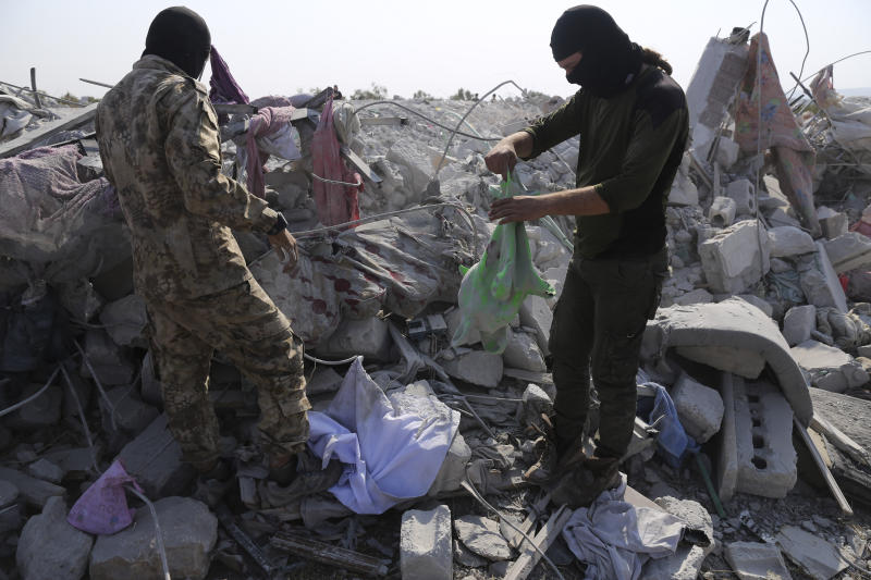 FILE - In this Oct. 27, 2019, file photo, people look at a destroyed houses near the village of Barisha, in Idlib province, Syria, after an operation by the U.S. military which targeted Abu Bakr al-Baghdadi, the shadowy leader of the Islamic State group. The Islamic State group seemed largely defeated last year, with the loss of its territory, the killing of its founder in a U.S. raid and an unprecedented crackdown on its social media propaganda machine but tensions between the U.S. and Iran in the region provide a comeback opportunity for the extremist group. (AP Photo/Ghaith Alsayed, File)