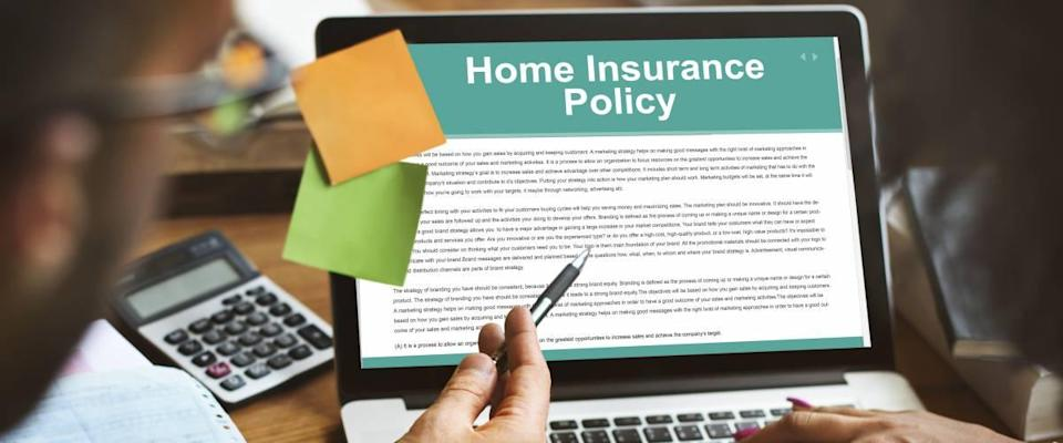 Two people looking at a laptop screen that says Home Insurance Policy.