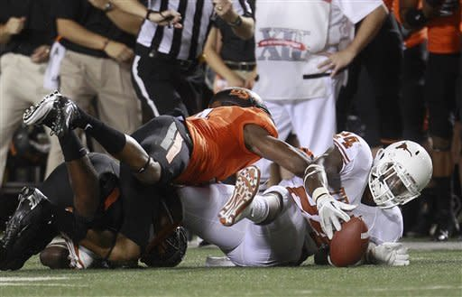 Texas running back Joe Bergeron (24) recovers his own fumble as Oklahoma State cornerback Justin Gilbert (4) reaches for it during the second quarter of an NCAA college football game in Stillwater, Okla., Saturday, Sept. 29, 2012. (AP Photo/Sue Ogrocki)