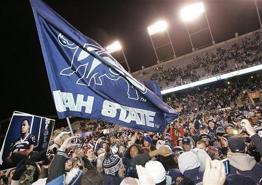 Utah State fans celebrate on the field after defeating Toledo in an NCAA college football game on Saturday, Dec. 15, 2012, in Boise, Idaho. Utah State won the Famous Idaho Potato Bowl game 41-15. (AP Photo/Matt Cilley)