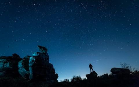 A plane and a satellite passing by a man stargazing at Brimham Rocks in Yorkshire as the Orionid meteor shower reached its peak - Credit: Danny Lawson/PA