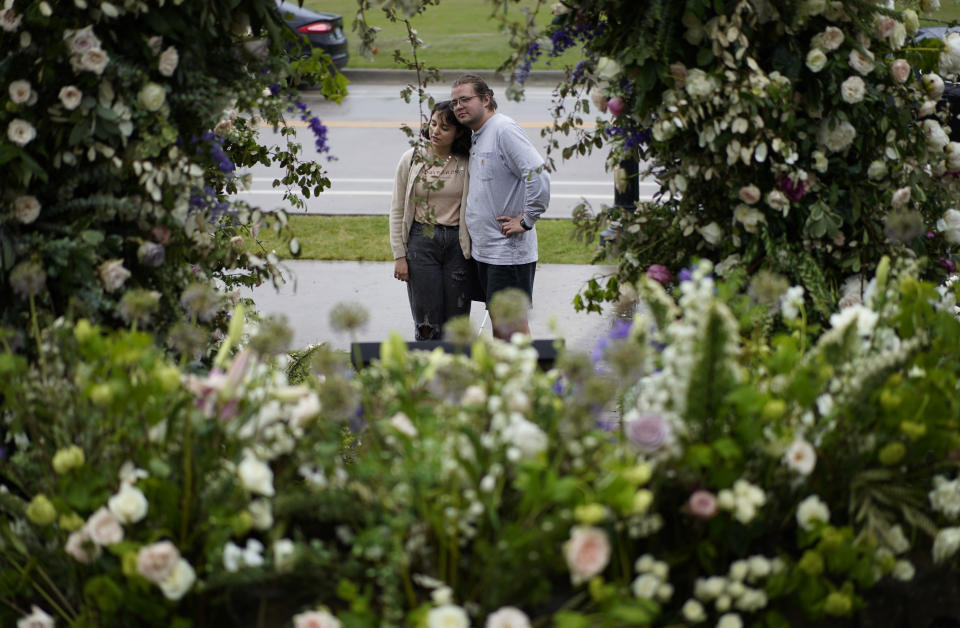 Ana Nunez, left, and Connor Coney embrace as they visit flowers left at a memorial for the Tulsa Race Massacre near the historic greenwood district during centennial commemorations of the massacre, Monday, May 31, 2021, in Tulsa, Okla. (AP Photo/John Locher)
