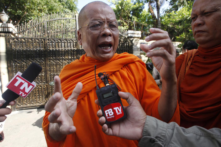 Cambodian Buddhist monk Sem Sovandy, center, talks with local journalists in front of the house of Kem Sokha, former leader of now dissolved opposition Cambodia National Rescue Party, in Phnom Penh, Cambodia, Monday, Sept. 10, 2018. Kem Sokha was released on bail Monday after being jailed for a year on a treason charge, a government spokesman said. A small crowd has gathered outside his home in Phnom Penh but so far he hasn't been seen. His whereabouts are, as yet, unclear. (AP Photo/Heng Sinith)
